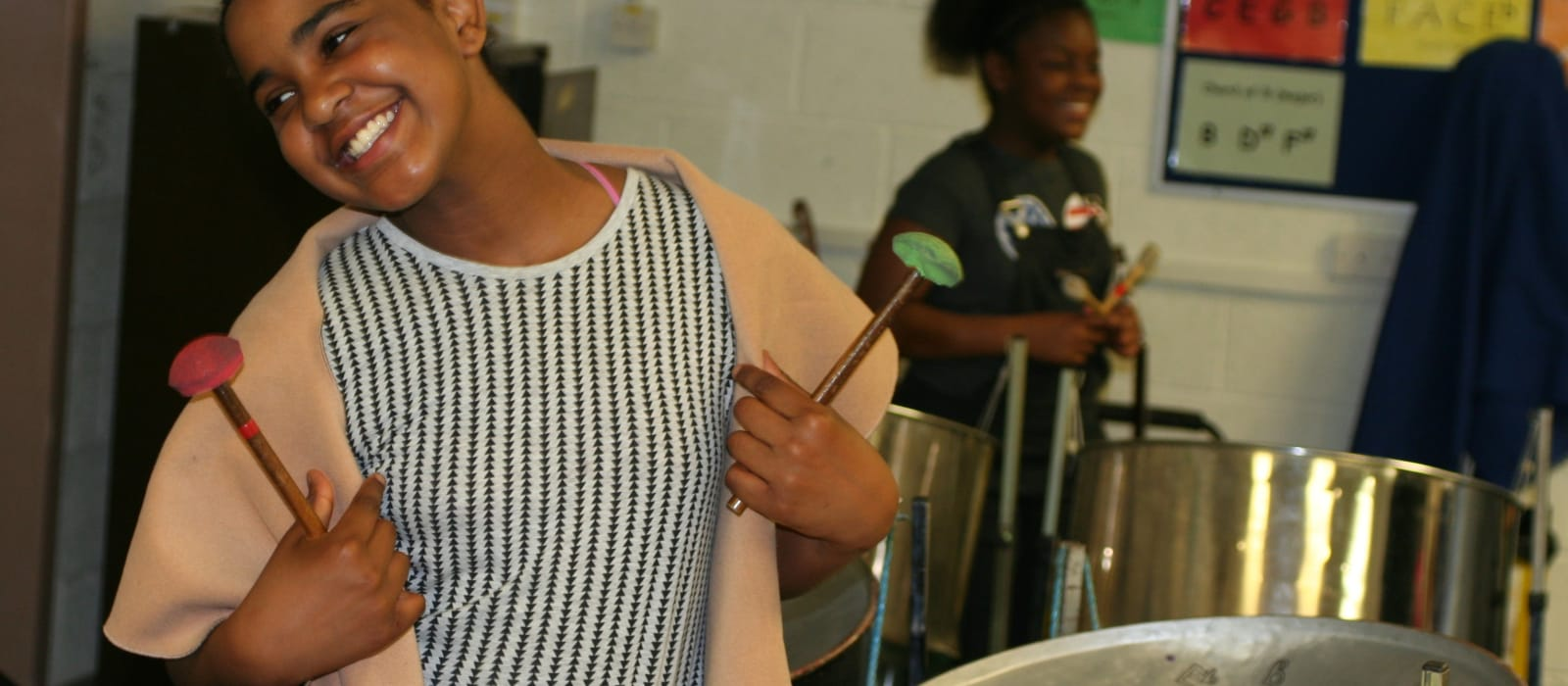 A young girl stands in front of a steel pan smiling