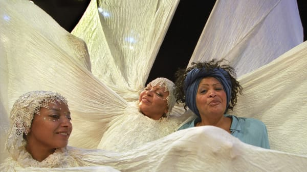 Carnival Messiah. Three black ladies singing amongst swarths of white fabric.