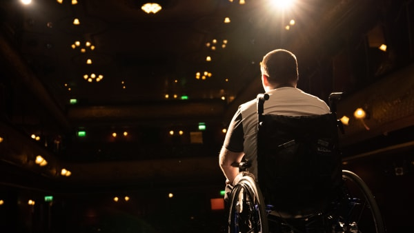 A young man in a wheelchair on stage looking out towards the audience