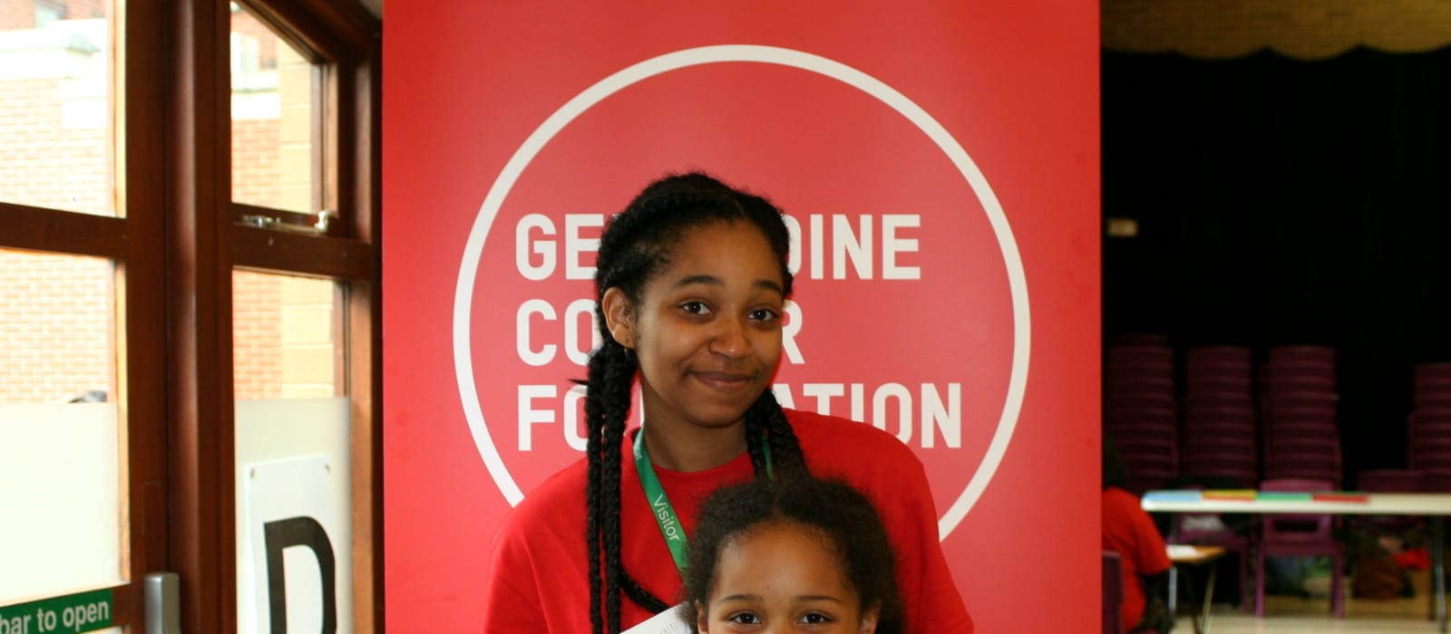 A young black girl stands with a young child in front of the GCF banner.