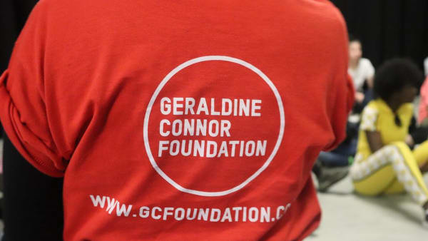 The back of someone wearing a red t-shirt with the GCF logo on