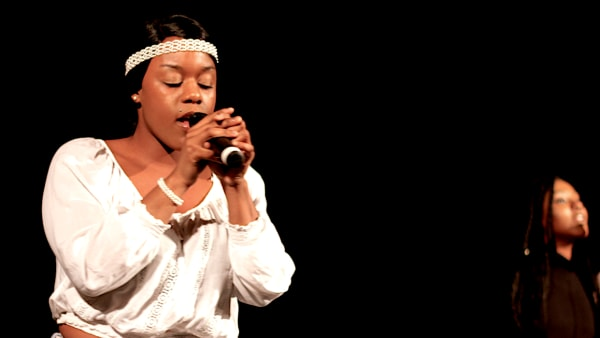 A young woman sings in front of a black background