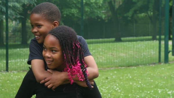 Two black children, a boy and a girl. the girl is giving the boy a piggy back.